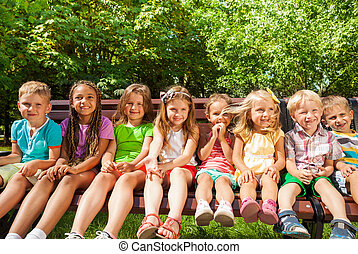 Kids in row on the bench, summer park