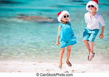 Kids in Santa hats at the beach