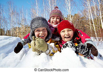 Kids in snow - Happy children in winterwear laughing while ...