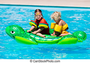 Kids in swimming pool with inflatable toy - Happy little...