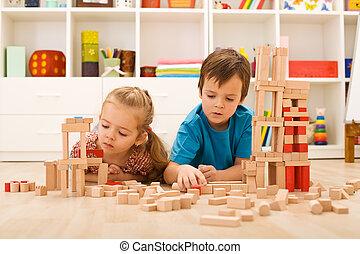 Kids inspecting their wooden block buildings
