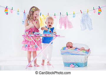Kids ironing clothes for baby brother - Newborn child on...