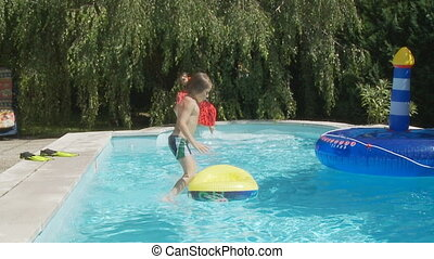 boy and girl jumping in swimming pool in slow motion