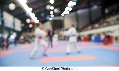 Kids karatekas fight on karate competitions, slow-motion de-focused sport background