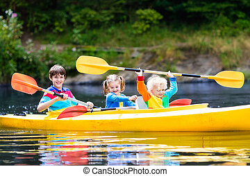 Kids kayaking on a river - Happy family with three kids ...