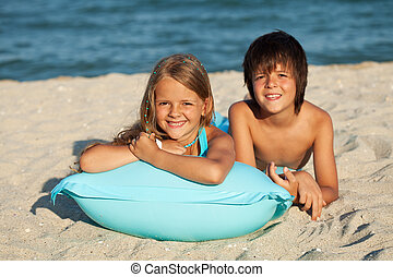 Kids laying in the sand on a beach