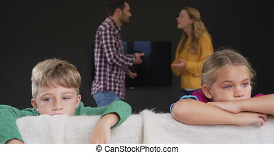 Kids leaning on sofa while parents arguing in background at ...