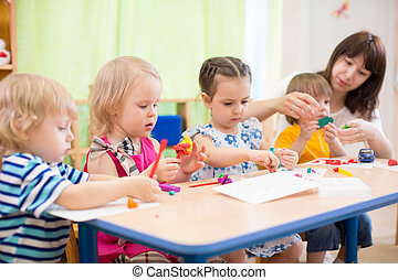 kids learning arts and crafts in kindergarten with teacher -...