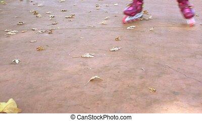 Kid's legs in inline skates. Slow motion