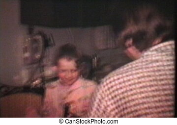 An excited brother and his two little sisters eagerly explore the kitchen in search of hidden Easter candies and treasure. (Scan from archival 8mm film)