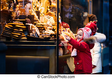 Kids looking at candy and pastry on Christmas market -...