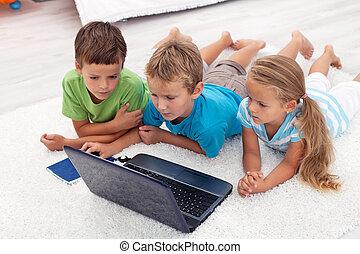 Kids looking at laptop computer - Three kids looking at...
