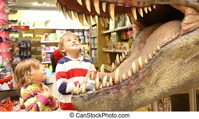 kids looks at mouth of toy dinosaur - two kids boy and...