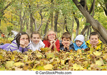 kids lying on leaves
