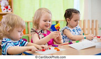 Kids making arts and crafts. Children in kindergarten. - ...