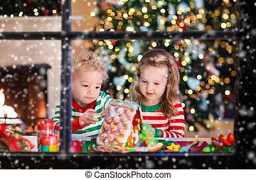 Kids making Christmas ginger bread house