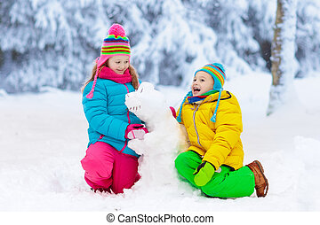 Kids making winter snowman. Children play in snow.