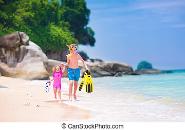 Kids on a beach - Two happy children, teenager boy and a...