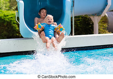 Kids on a water slide in swimming pool - Happy boys, two...