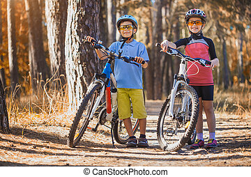 kids on abicycles in the sunny forest. happy children cycling outdoors in helmet