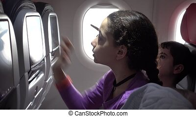 Kids on airplane using In flight entertainment known as IFE...