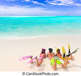 Three sibling children in bathing suits laying on the beach wearing flippers and snorkels by the water.