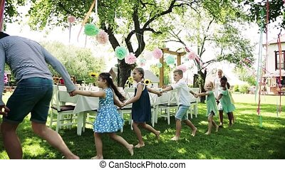 Kids on birthday party playing outdoors in garden in summer...
