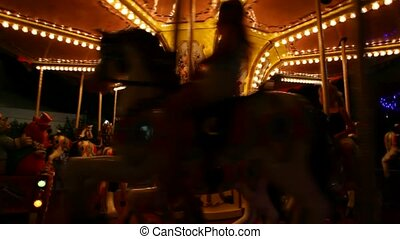 kids on carousel merry-go-round amusement ride with galloping horses