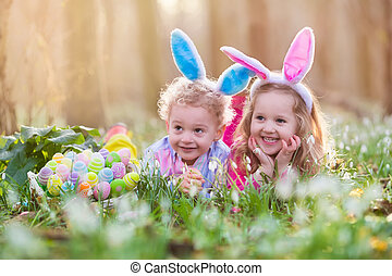 Kids on Easter egg hunt in blooming spring garden. Children ...