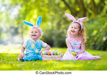 Kids on Easter egg hunt - Little boy and girl having fun on ...
