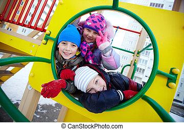 Kids on playground - Happy kids in winterwear looking at ...