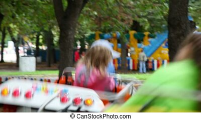 kids on rotating carousel amusement merry-go-round with cars in city park