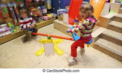 kids on seesaw in shop