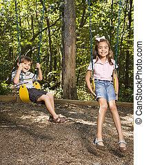 Kids on swing set. - Hispanic boy and girl on swing set...