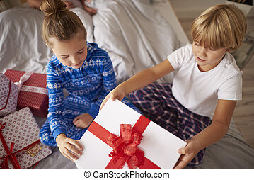 Kids opening big Christmas gift in the bed