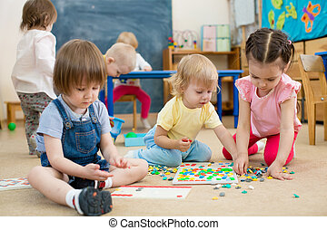 kids or children playing mosaic game in kindergarten room -...