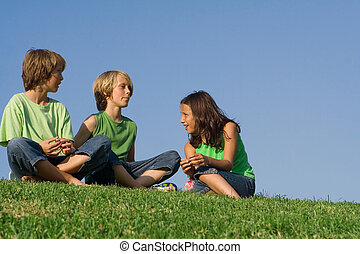 kids or children sitting outside on grass chatting,