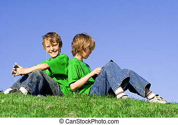 kids outdoors in summer, reading and listening to music