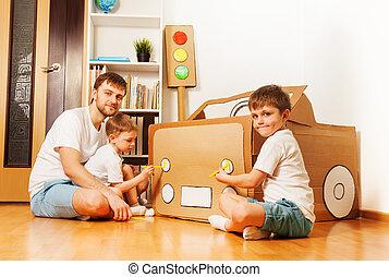 Kids painting headlights on toy cardboard car