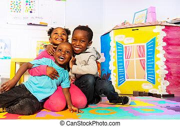 Kids play and hug in kindergarten room