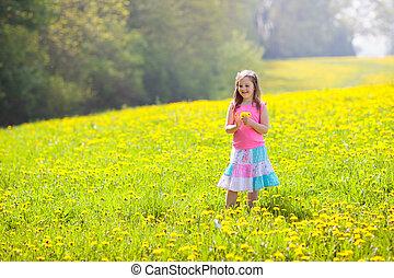 Kids play. Child in dandelion field. Summer flower