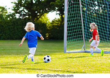 Kids play football. Child at soccer field.