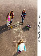 Kids play hopscotch - Group of kids jumping on the Hopscotch...