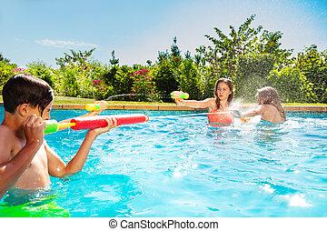 Kids play in swimming pool shooting water gun