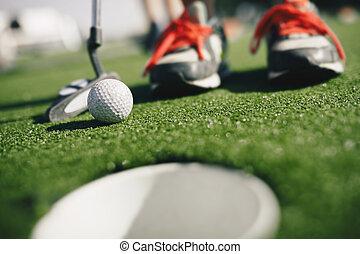 Kids play mini golf. Close-up image of player in snickers with mini golf club and white golf ball. e cup in the foreground Gold hole th