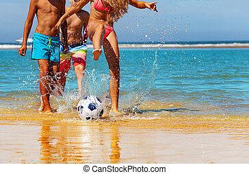 Kids play soccer on the beach near water closeup