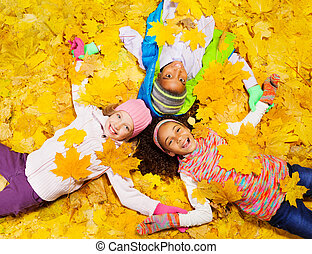 Three kids, girls and a boy laying and smiling on the ground covered with autumn maple orange leaves laying on the ground