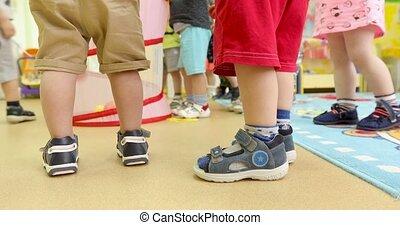 Unknown children stand and play in kindergarten - Kids play...