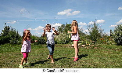 Kids play with soap bubbles outdoor