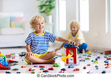 Kids play with toy cars. Children playing car toys